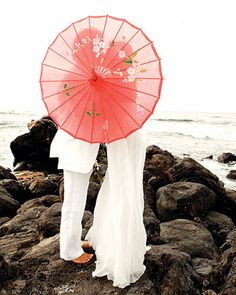 A couple shield themselves with a bright parasol on the beaches of Maui...we have a  Similar photo from our wedding... so pretty