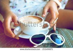 Close up fashion image of woman holding  white cup of her morning cappuccino, wearing white stylish dress, and put her vintage heart sunglasses to the table, enjoy her time alone. Instagram colors.