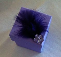 Purple favor box with purple feather and diamante flower detail.