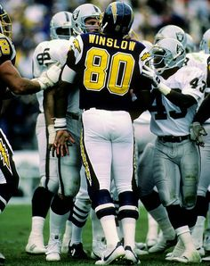 Defensive End Howie Long #75 and Tight End Kellen Winslow #80 exchange pleasantries during the Chargers' 40-34 overtime win in 1985.