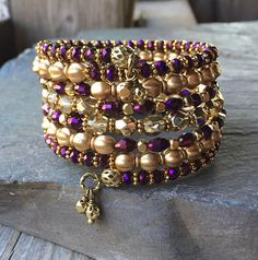 This 7 coil bracelet is made with brass memory wire - will adjust to the size of your wrist and no chance of breaking. This will ensure you will have this bracelet for a long time. Materials include 6mm golden matte Czech glass melons, 6mm golden foiled Czech glass, 4mm metallic purple faceted glass beads and assorted golden accenting spacers. Finished off with a couple tiny wrapped matching bead dangles on each end. Will fit most teen and adult sized wrists.  This bracelet is on the medium…