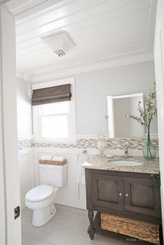 Love the details in this small powder room - the bead board ceiling and tile trim eclecticallyvintage.com