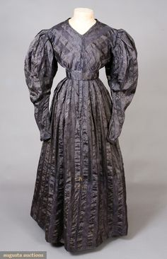 GAUZE JACQUARD SILK MOURNING GOWN, 1830s November, 2007 -Tasha Tudor Historic Costume Collection New Hope, PA Striped and patterned silk, every 1890-1920 stripe sheer in deep purple alternating with woven leaf pattern in black, collarless, V neckline, center front opening, full sleeves tapering to narrow banded cuff with one button, sleeve cap inner-lined with stned cotton, skirt pleated into inset purple silk satin waistband, deep purple silk bodice lining and deep hem facing,