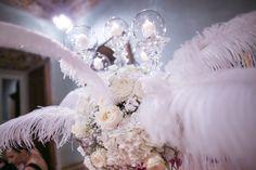 Il centrotavola di fiori bianchi , fucsia e piume .