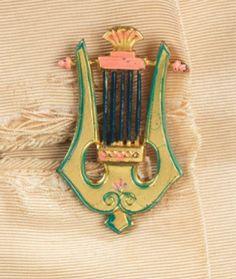 """Bouton de la collection """"Musique"""" (fall 1939) , représentant une lyre miniature. Métal. Gros plan"""