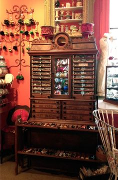an early spool cabinet filled with vintage buttons and trims. Craft room storage bliss!