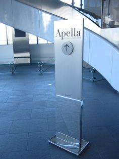 This custom meeting space pylon features a polished aluminum base, satin aluminum riser, and a rotating disc.