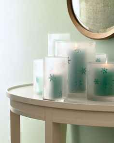 "You can ""frost"" inexpensive cylindrical glass vases with glass-frosting spray to make these candleholders. Use a snowflake craft punch to cut shapes from a self-adhesive laminating sheet. Affix snowflakes to outside of each vase. Apply glass-frosting spray (available at home-supply stores) in an even layer all over outside of vase; let dry. Using tip of a craft knife, careful..."