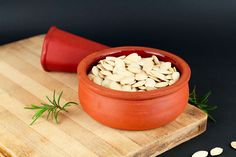 Pumpkin seeds and rosemary plant on wooden chopping board #food
