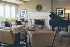 Sophisticated and contemporary living room design with traditional fireplace and baby grand piano.