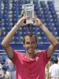 Lukas Rosol, of Czech Republic, raises the trophy after defeating Jerzy Janowicz, of Poland, in the championship match of the Winston-Salem Open tennis tournament in Winston-Salem, N.C., Saturday, Aug. 23, 2014. Rosol won 3-6, 7-6 (3), 7-5. (AP)