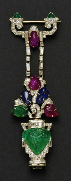 "Art Deco ""Tutti Frutti"" Pendant Watch, Mauboussin, France, designed as a carved emerald flowerpot with carved ruby, sapphire, and emerald blossoms, and transitional-, old single-, baguette-, and fancy-cut diamonds."