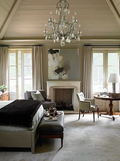 Shiplap ceilings and grayish-beige paint add a rustic feel to this bedroom, while the crystal chandelier gives it a dose of modern glam!