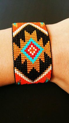 Two filaments of stocky silver grains make an elegant wrap for the wrist. The little nuggets are enhanced with an imprinted gourd-like beauty that hangs near the clutch. Native Beading Patterns, Native Beadwork, Beaded Jewelry Patterns, Loom Patterns, Diy Bracelets Easy, Loom Bracelets, Ankle Bracelets, Handmade Bracelets, Silver Bracelets