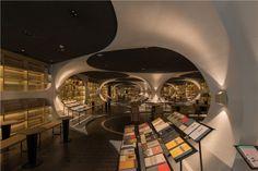Moderna, a biblioteca tem luz baixa, ambiente aconchegante e elementos futurísticos – tudo projetado pelo escritório de arquitetura XL-MUSE