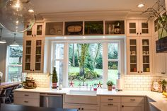 White farmhouse style kitchen with lots of storage. The counter top flows into the window sill to give a little more space behind the sink.