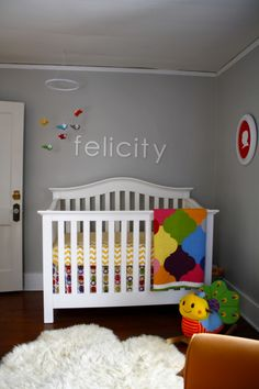 A neutral gray wall is a great backdrop for brightly colored accents  #gray #rainbow #nursery