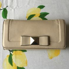 Kate spade wallet Good condition has some signs of wear on the middle of the bow. The colors are cream and black with gold tones of metal has a ton of life left kate spade Bags Wallets