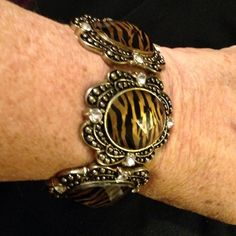 Tiger striped Bracelet Tiger stripe bracelet with black and gold medal enhanced  on each side with a beautiful rhinestone. Stretchy so it fits most sizes Jewelry Bracelets