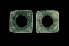 A pair of square earflares. Maya A.D. 250-850. carved in the shape of a four-petaled flower. Although they are the same size, one is carved from a mottled green jadeite and the other is carved from a more uniform, dark green jadeite.