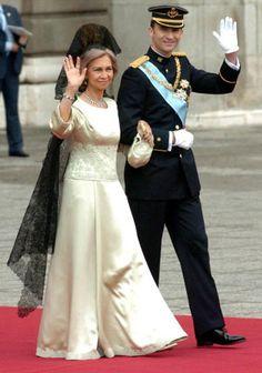 La reina Sofía, con una espectacular mantilla negra, lució un diseño de Margarita Nuez en satén color perla con bordados a tono en el talle y cuello redondo. Sobre éste un magnífico collar de brillantes, esmeraldas y pequeñas perlas