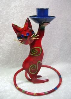 Cat Candle Holder Metal Sculpture Red Green Spiral Playful Unique  metal sculpture taper candle holder in the shape of a cat.  This cat is deep red in color with playful green spirals on its body, and its eyes are brilliant blue.  The cat's tail curves around the bottom and serves as the sturdy base, and the whiskers can be adjusted as you wish.   Candle holder measures about 7 and 1/8 inches tall, and the base goes to about 5 inches wide at the widest diameter. Metal, Sturdy, Red Green, Novelty Lamp, Cat Candle Holder, Taper Candle Holders, Metal Sculpture, Candles, Metal Candle Holders