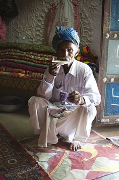 Turbanned man sipping tea from saucer in tribal home in front of piles of hand embroidered quilts, Soyla, Kachchh, Gujarat, India,