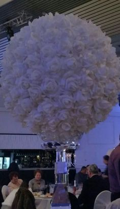 Fake white roses pinned on a polystyrene ball. Great idea for table centerpiece.