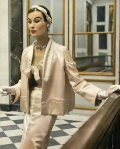 1952 Myrtle Crawford in pale pink satin evening suit, the slender dress is worn under a box jacket, by Christian Dior
