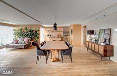 Madeira aquece a área social integrada após a reforma - A amplitude do terraço de 112 m² permitiu dividi-lo em diferentes recantos, cada qual com sua função. Dessa forma, enquanto batem papo na cozinha gourmet, os adultos podem ficar de olho nas crianças brincando no sofá.