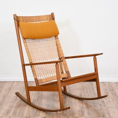 This mid century modern rocking chair is featured in a solid wood with a gorgeous teak finish. This rocker is in great condition with a high back, woven details and a removable mustard yellow cushion. Stylish and unique chair perfect for a nursery or kids room! #midcenturymodern #chairs #rockingchair #sandiegovintage #vintagefurniture