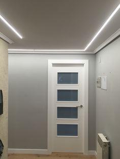 Hall iluminado con tiras de LEDs empotradas en el techo.
