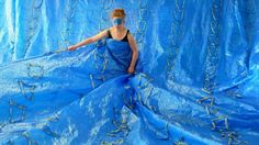 "The British-born artist stitched together 555 blue Ikea bags, the 59 cent ones.    Ida-Marie, constructed the gown for the opening group show in a Zurich Gallery using the neon yellow handles as straps for her shoulders; she let the rest of the voluminous patchwork of plastic wrap around the room.     Corell's ""ID(E)A dress"" is part of ""Oh, Plastiksack."""