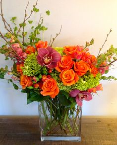 Green Bouquet Floral Design; flower arrangement of orange roses, green hypericum, magenta cymbidium orchids, pink snapdragons, mambo spray roses