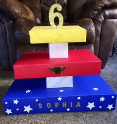 Wonder Woman Cupcake Tower made from 3 different sized clothes gift boxes (mine happened to all be Dillard's) wrapped in tissue paper stacked with 2 different sized square boxesfrom party city. Hot glued, stabilized with dowels & 100s of Walmart bags shoved inside (so the boxes don't end up saggy or tilting when you put your cupcakes on). And then Wonder Woman themed & name stickers from Hobby Lobby stuck accordingly. With a doweled #6 on top. Enjoy :]
