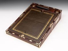 Edwards Kingwood Writing Box writing surface, 2 brass screw top ink wells & section for holding pens. Bottom half of writing surface has cross ribboned back & storage area & reading rail. Storage under top half writing surface & hidden compartment with 2 drawers accessed by removing the right inkwell and pressing down on the base of compartment. Under pen tray are 2 gilt brass candle sconces for holes on front edge of box.