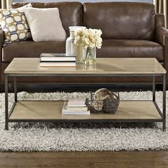 Arrange framed photos and stack art books on this understated coffee table, featuring a 2-tiered design with planked wood details.