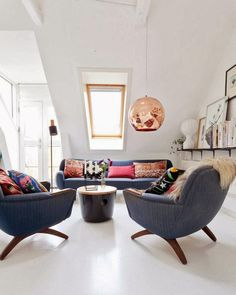 danish loft: skylight; white walls, blue chairs/sofa; bright room; pink and copper accents