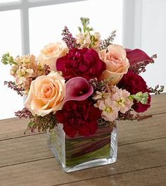 Best Wishes and Congratulations - FTD Share My World Bouquet - The FTD Share My World Bouquet blooms with modern sophistication and elegance to bring your special recipient a truly exquisite gift. Peach roses, peach stock, burgundy mini carnations and plum mini calla lilies are simply fantastic accented with heather stems and seated in a clear glass cubed vase. Variegated ti leaves and red flax leaves are used to line the inside of the vase for an appealing look making this brilliant bo...