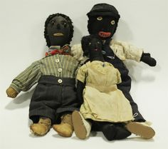 """Garths   Full Details for Lot 151 THREE EARLY BLACK CLOTH DOLLS WITH WOOL HAIR. American late 19th century dolls with stitched features and wood hair, one with shoe button eyes & leather hands & feet. All are hard stuffed and in early clothing. Girl has earrings and nubby hands. Larger boy has fabric mouth and pronounced nose, comma hands and leather shoes. Some staining and a few small holes. 11""""-15"""" in length. Estimate $ 200-400"""