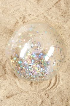 A clear beach ball by Pool Candy™ featuring iridescent silver confetti enclosed in the ball.
