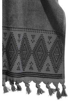 Serviette avce broderies: Serviette en coton éponge souple. Modèle avec motif brodé et pompons à la base. Patte de suspension sur une largeur.