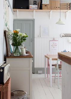 Kitchen dining area - white wooden floor, copper painted radiator & vintage sideboard.