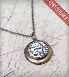 "This custom brass locket necklace features a vintage map inset. Choose your town or city, and wear the locket necklace with pride, a thoughtful homage to your hometown, where you met your true love, or a favorite vacation destination. These delicate necklaces are handmade with oxidized brass and vintage maps from all over the world.  Each locket, which measures just under 3/4"" in diameter, comes attached to a matching 18"" chain."