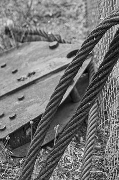 A photograph of an old cable and a rusted pulley in black and white. To purchase please go to http://memoriesoflove.imagekind.com