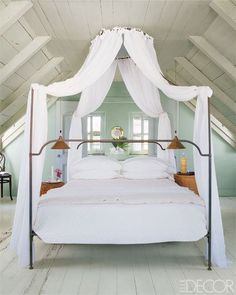Dressed with IKEA curtains, a wrought-iron lit à la polonaise with an eight-foot-tall canopy takes center stage in the master bedroom of Tom Scheerers 200-year-old cottage on Harbour Island in the Bahamas. Painted in pastel green, the room is kept shady and cool by louvered shutters.
