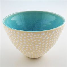 Wheel-thrown ceramic bowl with glossy-white raised spots dotting the creamy stoneware exterior.  The interior is glazed in a glossy Argentine blue.