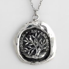 Fidelity Talisman Necklace  In French, this handcrafted talisman necklace reads Fidèle En Absence which means Fidelity in Absence. Pictured is a turtle dove perched on the tree of life, a symbol of interconnectedness and unity.