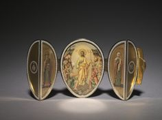 2/2 Imperial Red Cross Easter Egg, 1915. The front cross with the portrait of Tatiana serves as a clasp, securing the double opening doors. The front of the egg divides into two quarters when opened, reveals a triptych within. The central scene is the Harrowing of Hell, the Orthodox representation of the Resurrection. Saint Olga, the founder of Christianity in Russia is represented on the left wing of the triptych. The martyr Saint Tatiana on the right.