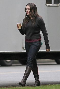 Love her look. Dark boots, jeans, black sweater & and just a touch of color (burgundy).